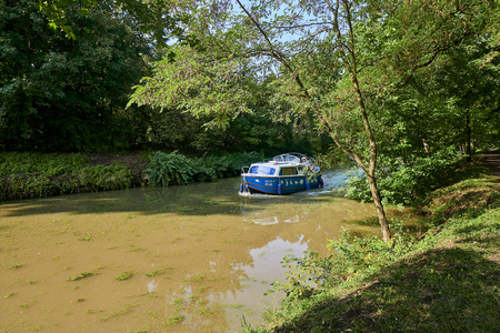 Straznice, Czech Republic - September 02, 2018: Baa Canal is a navigable canal on the Morava river in the Czech Republic. Blue and white motorboat on Baa Canal in the sunny summer day Editorial