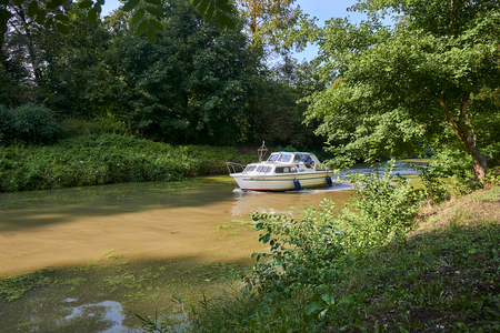 Straznice, Czech Republic - September 02, 2018: Baa Canal is a navigable canal on the Morava river in the Czech Republic. White motorboat on Baa Canal in the sunny summer day.