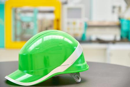 Green safety helmet on industrial background