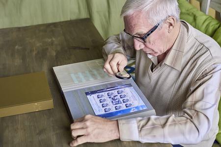 Senior man examines through an album