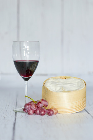Glass of red wine, red grapes and camembert cheese in a wooden box - vertical Фото со стока