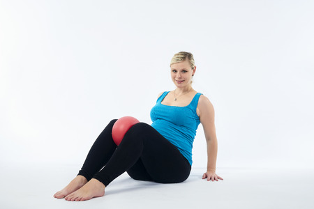 Young blondy pregnant woman does exercises Imagens