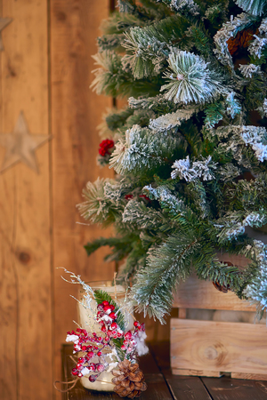 White Christmas candle holder decorated with pine cone and ashberry stick under Christmas tree on a wooden table Banque d'images - 114618940