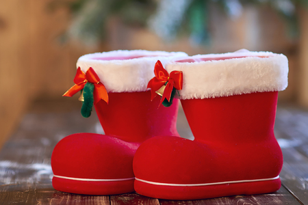 Red Christmas boot with white border and small bells on a wooden table Banque d'images - 114618941