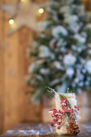 White Christmas candle holder decorated with pine cone and ashberry stick under Christmas tree on a wooden table Banque d'images - 114618942