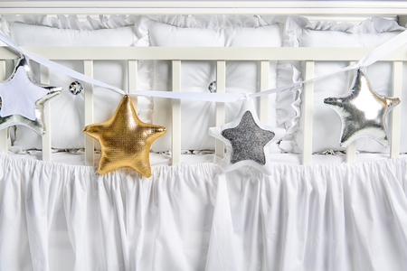Silver, gold and white star shaped pillows on a white baby cot Stock Photo