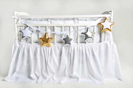 Silver, gold and white star shaped pillows on a white baby cot Standard-Bild - 114618948