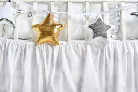 Silver, gold and white star shaped pillows on a white baby cot Banque d'images - 114618950