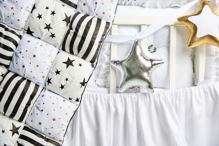 Silver and gold star shaped pillows and patchwork comforter on a white baby cot Banque d'images - 114618954
