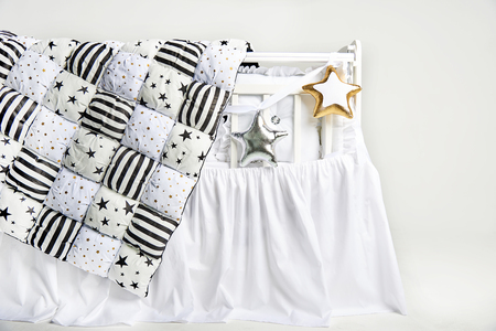 Silver and gold star shaped pillows and patchwork comforter on a white baby cot Standard-Bild - 114618955