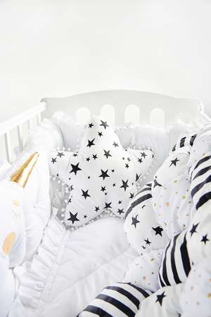 Cozy baby cot with star shaped cushion and patchwork comforter blanket with stars and black stripes Standard-Bild - 114618956
