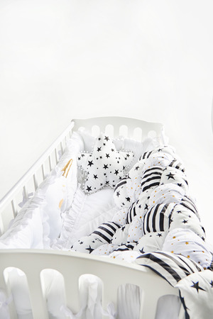 Cozy baby cot with star shaped cushion and patchwork comforter blanket with stars and black stripes Standard-Bild - 114618957