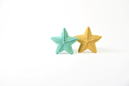 Yellow and blue-green knitted five-pointed star shaped pillows on white background - two pieces Standard-Bild - 114618493