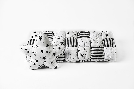 White patchwork (feather) comforter with black and gold stars and (black) stripes and white star shaped (soft) pillow with black stars Standard-Bild - 114618496