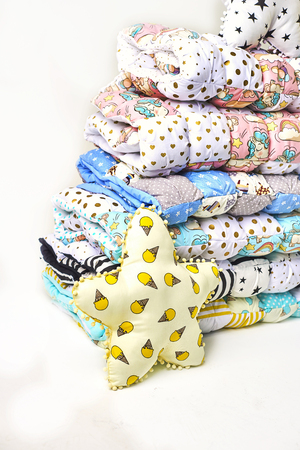 Patchwork and fashion concept - beautiful stack of colorful quilts, bedspreads stacked in several rows in height for storage, sale of stitched products on a white background Standard-Bild - 114618498