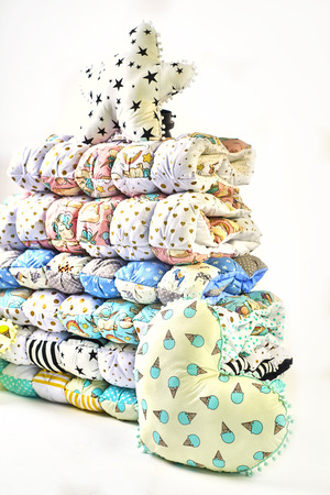 Patchwork and fashion concept - beautiful stack of colorful quilts, bedspreads stacked in several rows in height for storage, sale of stitched products on a white background Standard-Bild - 114618502