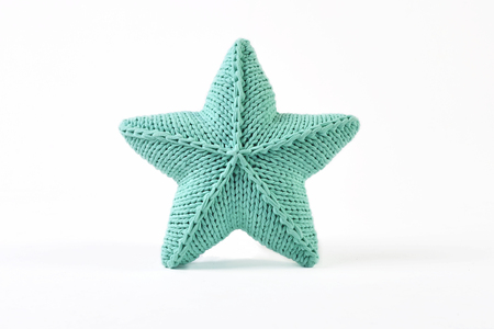 Blue-green knitted five-pointed star shaped pillow on white background Standard-Bild - 114618511