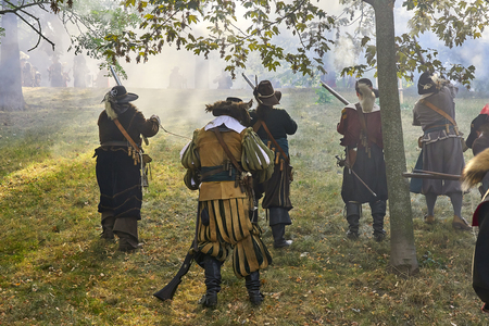 Brno, Czech Republic - August 18, 2018: Historical reenactment Day of Brno. Actors in historical Infantry costumes attack with muskets. Sun shines through gun powder smoke