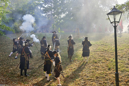 Brno, Czech Republic - August 18, 2018: Historical reenactment Day of Brno. Actors in historical Infantry costumes attack with muskets. Sun shines through gun powder smoke Banque d'images - 122970783