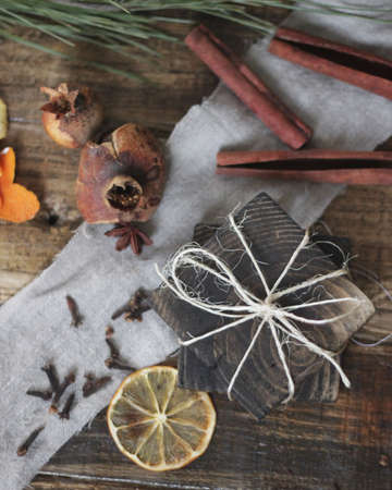 candle: Dried fruits on wooden rustic background. Christmas background contained of dried lemon, pomegranate, cloves, anise and cinnamon sticks