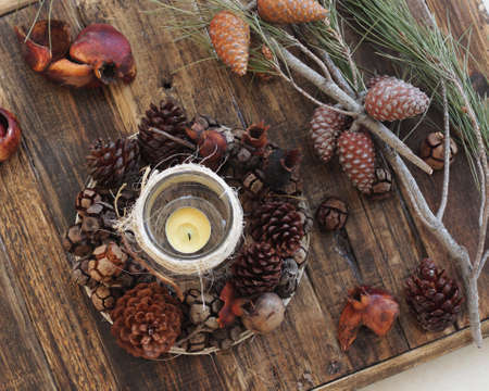 candle: Christmas decoration with candle and pine cones on wooden rustic background