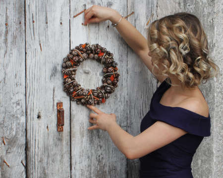 residence: A beautiful woman hanging a Christmas wreath on her home door. The girl in dark blue dress is hanging a cones rustic wreath on old white wooden door