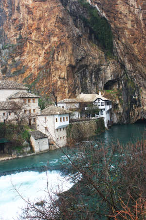 Dervish house on Buna spring with a small waterfall and a cave nearby in a winter day in Blagaj, Bosnia and Herzegovina