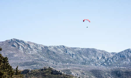 red paraplane in blue sky. Mountains view