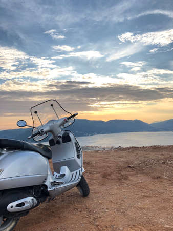 Scooter is parkied near the sea in sunset time. View of Boka Kotorska Bay from Lustica peninsula,