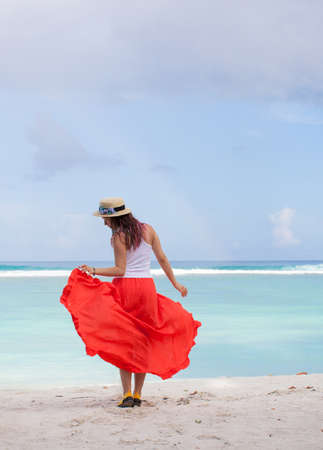 beautiful young woman in straw boater hat, red long skirt posing on Indian ocean beach on Maldive island