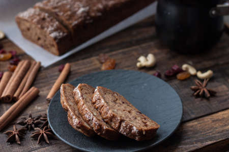 Homemade banana bread with anis star and cinnamon on a dark wooden background. Cup of tea and banana cake breakfast. Autumn winter cozy home