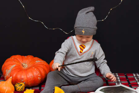 Little baby boy is reading a magic book in halloween time. Magic wand in a hand, black background and pumpkins.