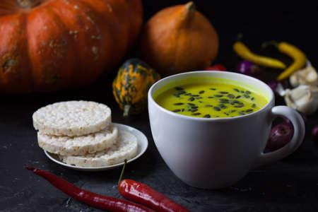 Pumpkin asian coconat cream soup. Autumn hot food. chili pepper, garlic, red onion, big pumpkin. Dark pgoto Stock fotó