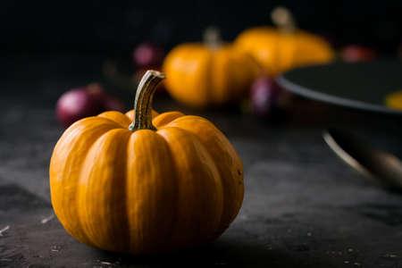 Pumpkin and orange cream soup with pumpkin seeds in black plate. Dark photo. Smakk pumpkin, chilly papper around. Stock fotó