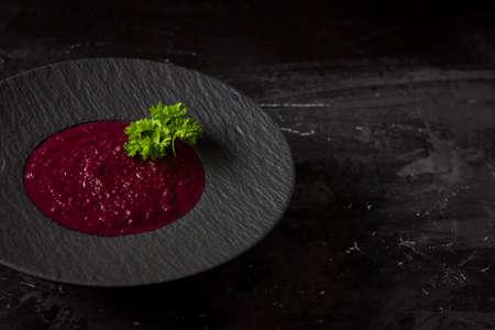 beetroot cream soup in black dish.  Dark food photo