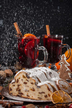 Traditional stollen cake and milled Hot wine with Christmas decorations background. Holiday dark photo.
