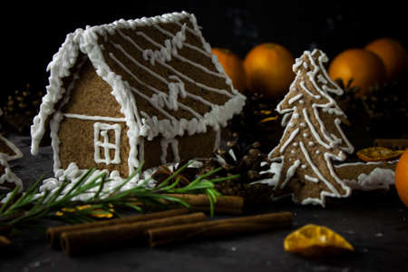 Homemade gingerbread house on black night background, ginger cookies. Christmas dark photo. Tangarines, anis stars, cinnamon sticks and cones. Sweet winter ginger cookies picture.
