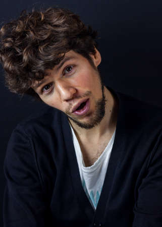 Curly man portrait on dark studio background.  tricksy emotional face Stock fotó
