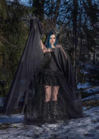Black queen. Blue hair woman portrait in forest. Fantasy photo