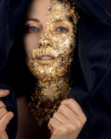 Closeup portrait of beautiful young woman with golden foil on face. Creative golden makeup on black background Stock fotó