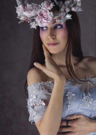 Fashion Portrait of Young Woman with Beautiful Flower Wreath Hairstyle and Fashion creative Makeup. Model with silk Blooming flower crown. Beauty salon background. Fairy tale magic lady.
