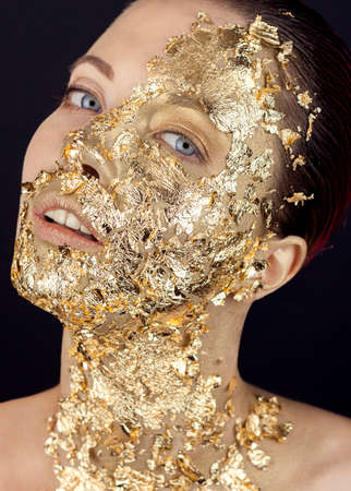 Closeup portrait of beautiful young woman with golden foil on face. Creative golden makeup on black background and tropical green monstera leaves.