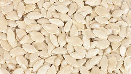raw superfoods pumpkin seeds on white background.