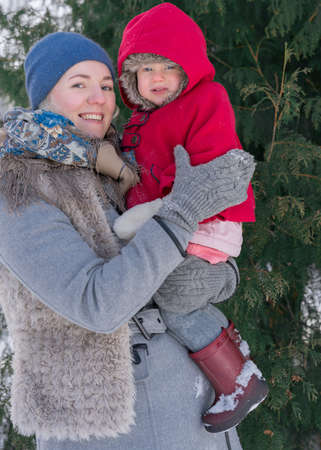 Two years old child in red coat at winter with mother.; Russian style village photo