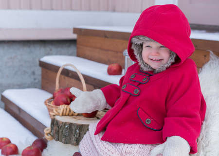 Two years old child in red coat at winter. Russian style village photo. Red apples in basket and snow Stock fotó