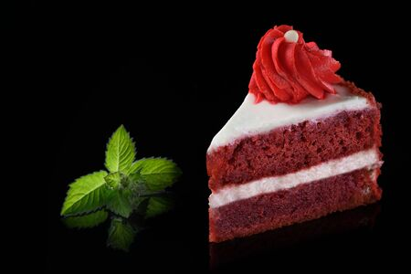 Stück Kuchen Roter Samt auf schwarzem Hintergrund. Minzblatt als Dekoration.