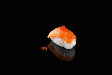 sushi of rice and red salmon fish on a black reflective background
