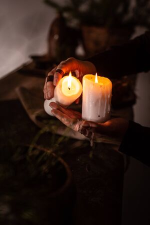woman in the image of a witch in an old dress holding a burning candle in her hands