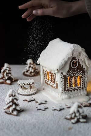 Gingerbread cookie house decorated with white glaze on a black background