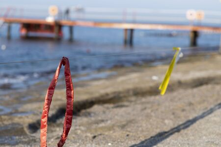 restrictive strip on the beach, red and yellow ribbons